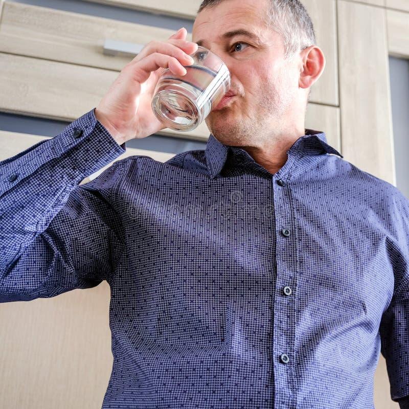 Mężczyzna cierpi od migren Iść brać migreny pigułkę Trzyma szkło woda migreny obraz stock