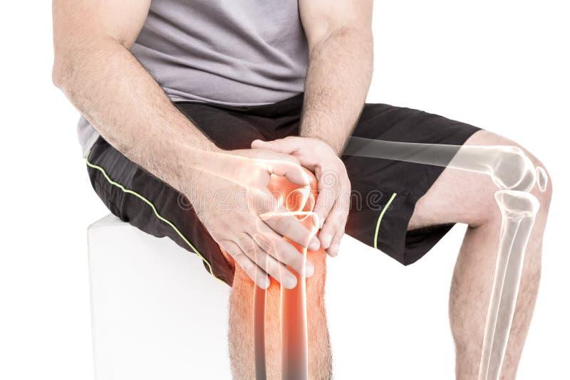 Mężczyzna cierpienie z kolano bólem podczas gdy siedzący przeciw białemu tłu obraz royalty free