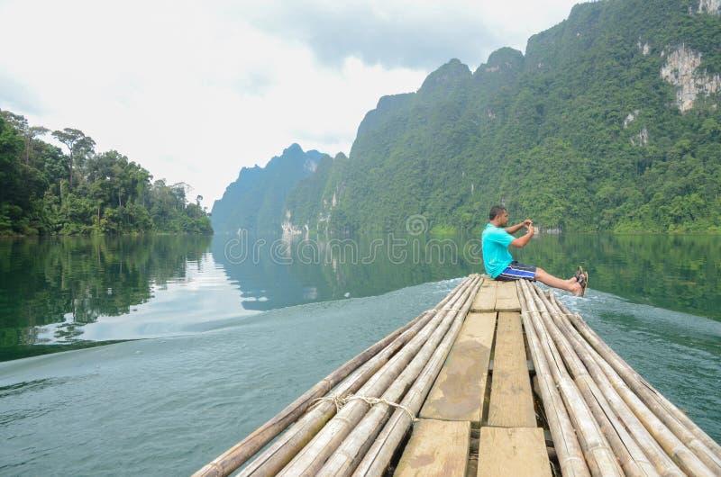 Mężczyzna cieszy się Pięknej natury scenicznego krajobrazowego widok na bambusowej łodzi przy Khao Sok parkiem narodowym który at obrazy royalty free