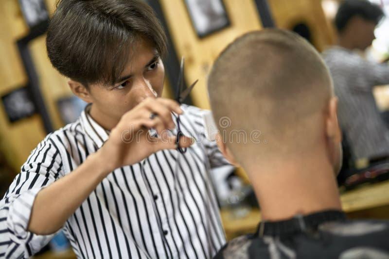 Mężczyzna ciie jego włosy w azjatykcim zakładzie fryzjerskim obrazy royalty free