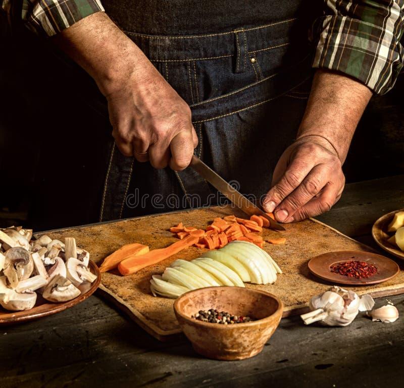 Mężczyzna ciie marchewki Blisko surowych warzyw r Wieśniak stylowa fotografia zdjęcia royalty free