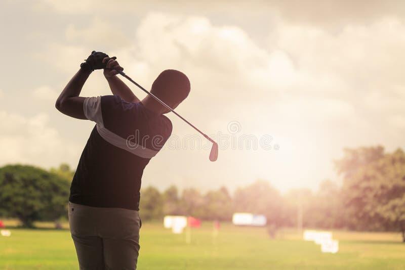 Mężczyzna ciupnięcia golfa strzał z klubem na kursie przy wieczór czasem zdjęcia royalty free