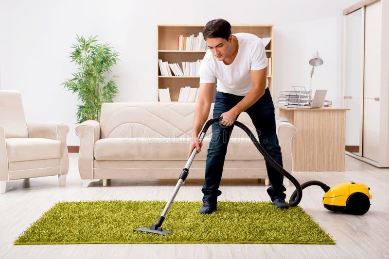 Mężczyzna cleaning dom z próżniowym cleaner fotografia stock
