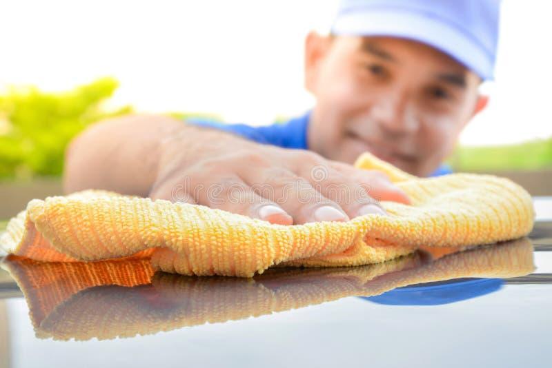 Mężczyzna cleaning samochód z microfiber płótnem fotografia stock