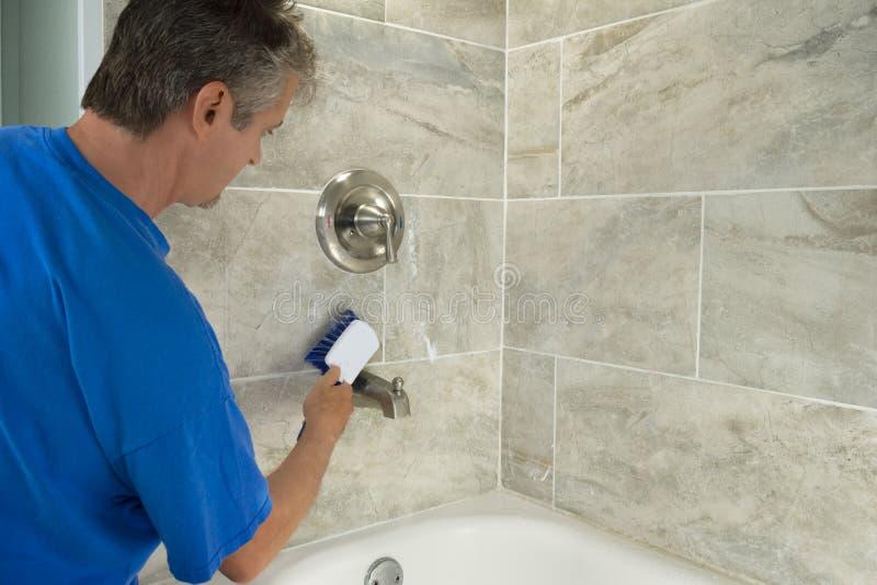 Mężczyzna cleaning wanny elementy wyposażenia z pętaczki muśnięciem i płytki obrazy stock