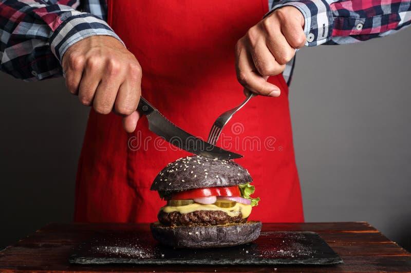 Mężczyzna cuttung hamburger zdjęcia royalty free