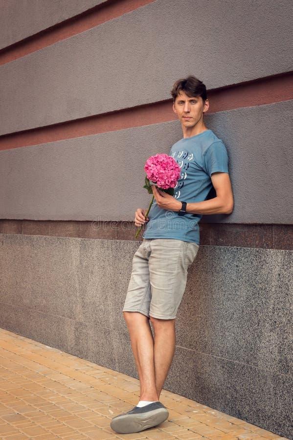 Mężczyzna czeka przy spotkania miejsca ukochanym Jest przyglądającym zamyśleniem przy kamerą W jego rękach trzyma różowej hortens zdjęcie stock
