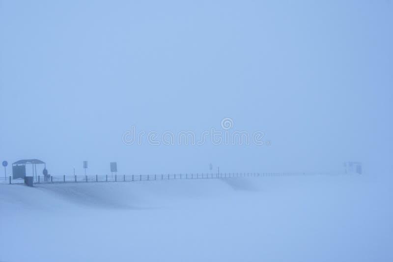 Mężczyzna czeka transport na śnieżnej drodze w mgle fotografia royalty free
