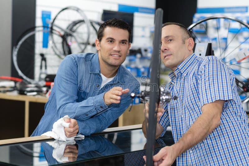 Mężczyzna czeki jechać na rowerze robią zakupy zanim kupujący w sportach zdjęcie royalty free
