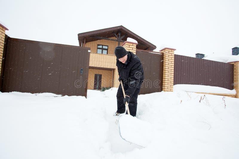 Mężczyzna czyści śnieżny przeszuflowywać obraz royalty free