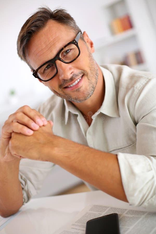 Mężczyzna czyta gazetę w domu z eyeglasses zdjęcia royalty free