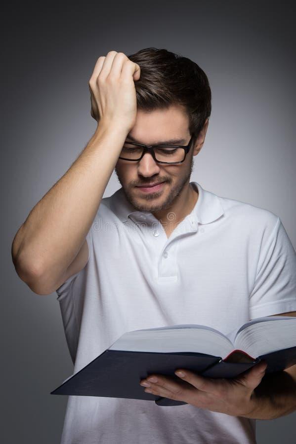 Mężczyzna czyta książkę. Portret młodzi człowiecy czyta hol i książkę obraz royalty free
