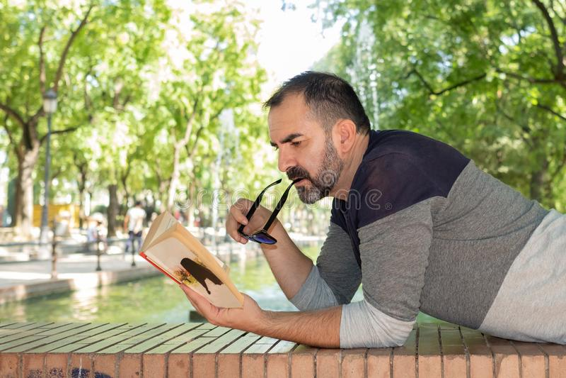 Mężczyzna czyta książkę w parku obraz royalty free