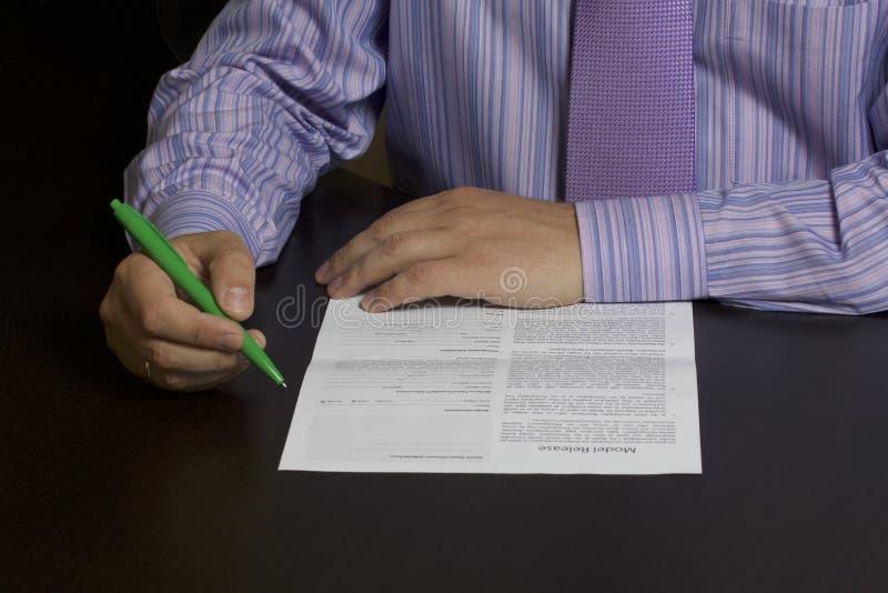 Mężczyzna czyta wzorcowego uwolnienie przed podpisywać je obrazy royalty free