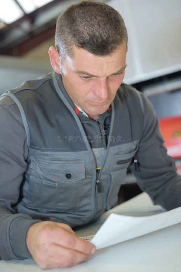 Mężczyzna czyta znacząco papier w warsztacie zdjęcia stock