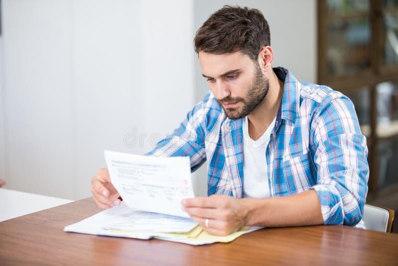 Mężczyzna czytania dokumenty podczas gdy siedzący przy stołem obrazy stock
