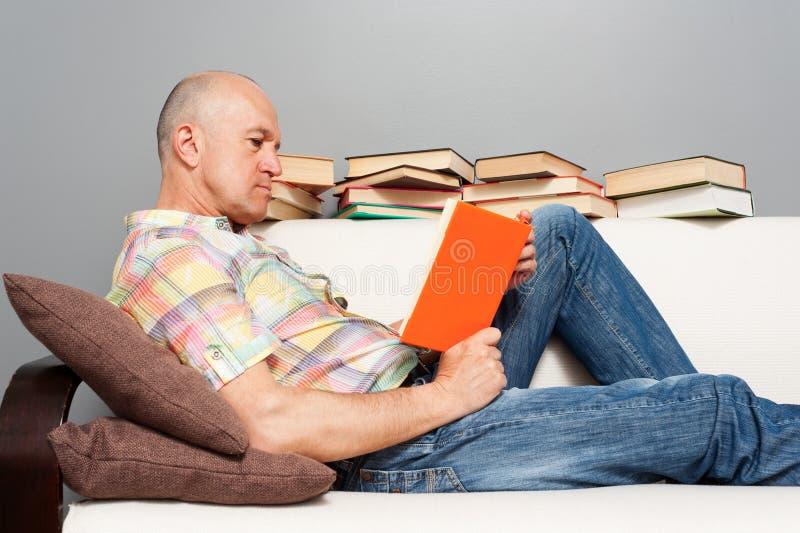 Mężczyzna czytania książka w domu obrazy royalty free