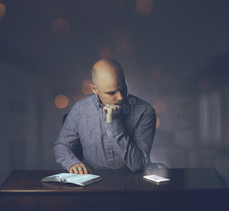 Mężczyzna czytelnicza biblia i rozpraszający uwagę zdjęcie royalty free