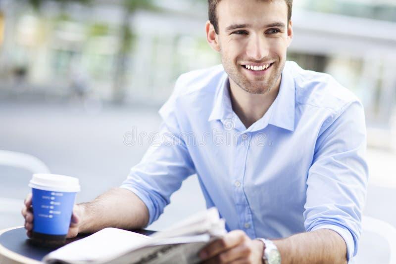 Mężczyzna czytelnicza gazeta przy plenerową kawiarnią fotografia royalty free