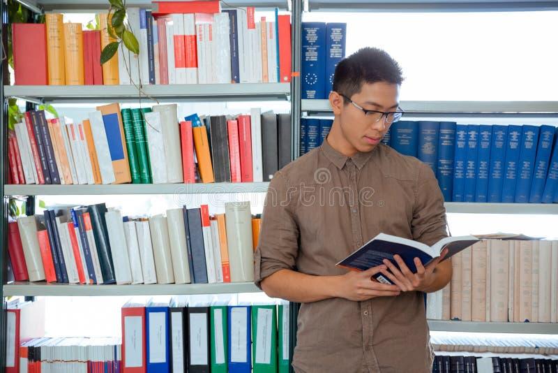 Mężczyzna czytelnicza książka w bibliotece uniwersyteckiej fotografia stock