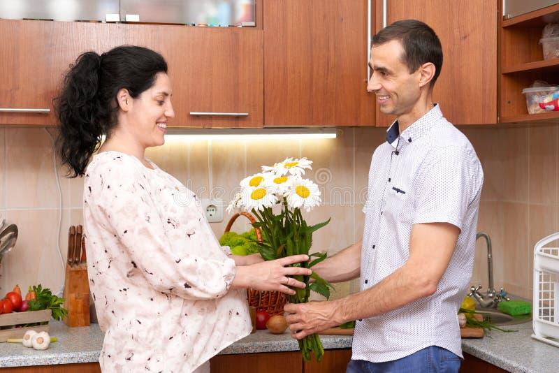 Mężczyzna daje chamomile kwiaty kobieta w ciąży, para w kuchennym wnętrzu z świeżymi owoc i warzywo, zdrowy karmowy pojęcie zdjęcia stock