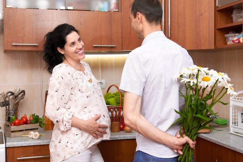 Mężczyzna daje chamomile kwiaty kobieta w ciąży, para w kuchennym wnętrzu z świeżymi owoc i warzywo, zdrowy karmowy pojęcie zdjęcia royalty free