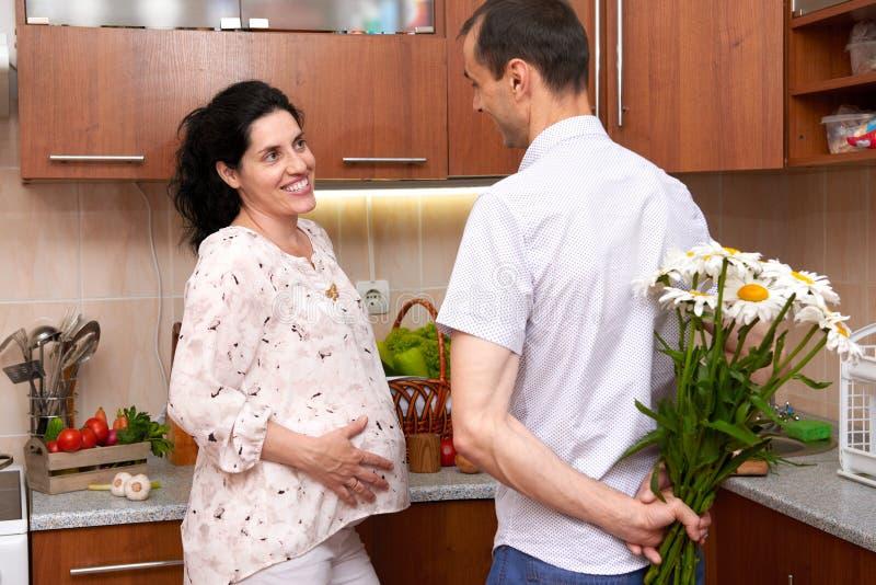 Mężczyzna daje chamomile kwiaty kobieta w ciąży, para w kuchennym wnętrzu z świeżymi owoc i warzywo, zdrowy karmowy pojęcie obrazy royalty free