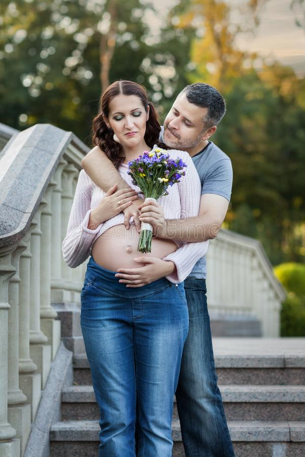 Mężczyzna daje jego młodej ciężarnej żonie bukietowi zdjęcie royalty free