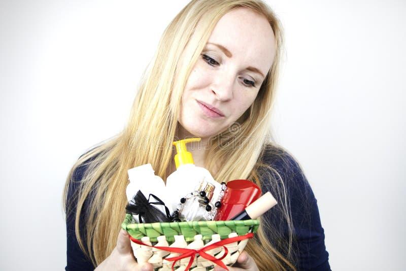 Mężczyzna daje pięknej dziewczynie prezentowi - kosz z kosmetykami i higiena produktami Przyjemna niespodzianka dla urodziny, wal obraz stock