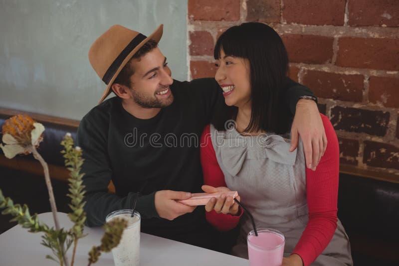 Mężczyzna daje prezentowi kobieta w kawiarni obrazy royalty free