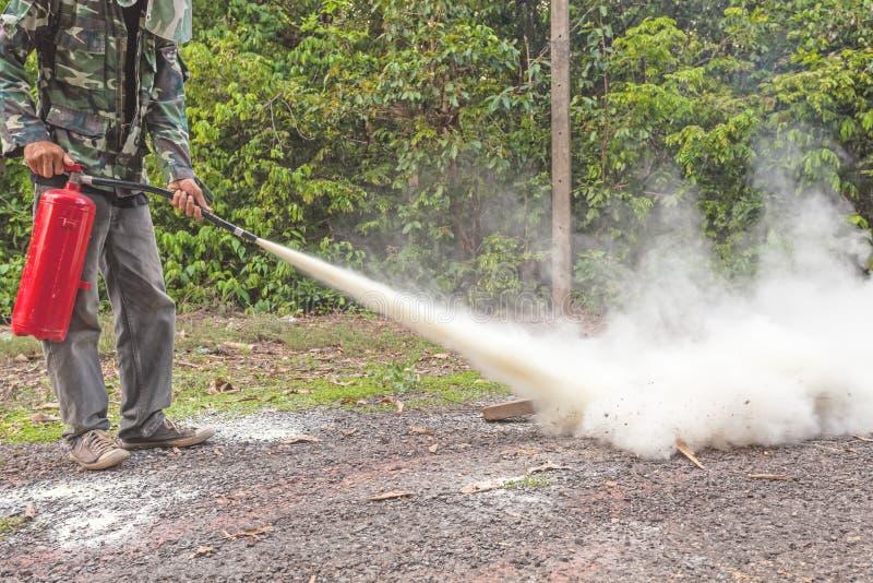 Mężczyzna demonstruje dlaczego używać pożarniczego gasidło fotografia royalty free