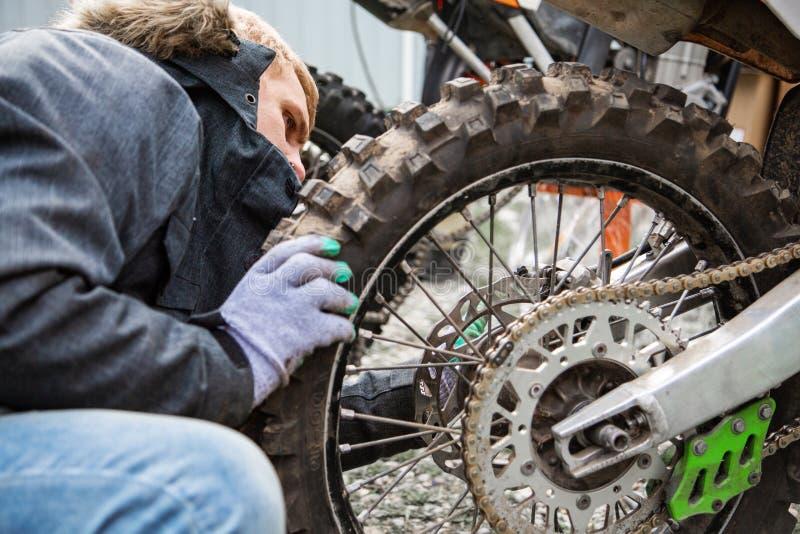Mężczyzna dociska koło motocyklu zakończenie up obraz royalty free