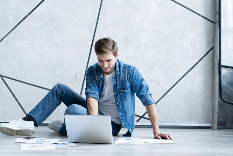 mężczyzna domowy działanie Przystojny młodego człowieka obsiadanie na egzamininować dokumencie i podłodze podczas gdy laptopu i d fotografia stock