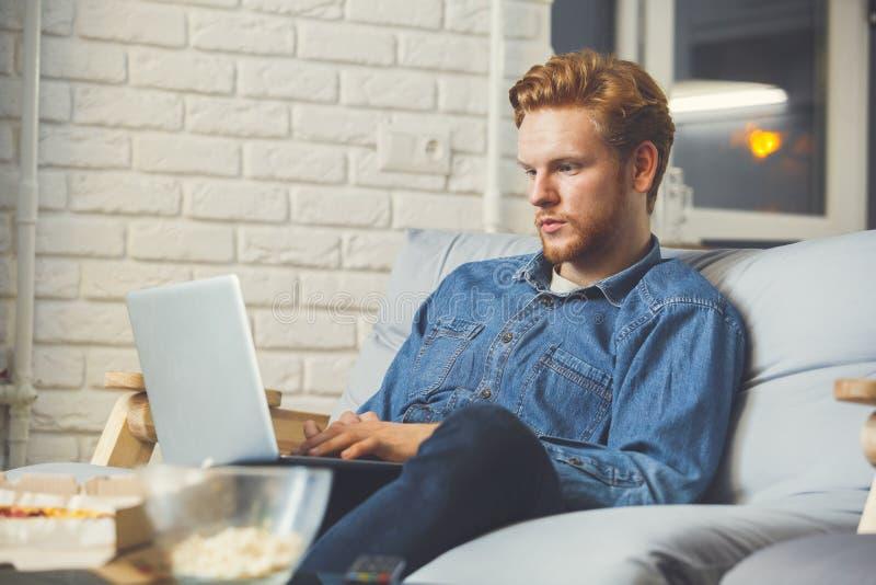 Mężczyzna dopatrywania sport na tv samotnym robić w domu zakładający się fotografia royalty free