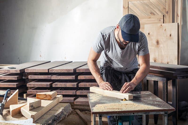 Mężczyzna dorówna drewnianą prętową mielenie maszynę obrazy stock