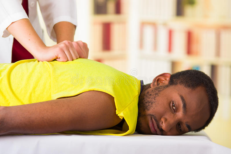 Mężczyzna dostaje fizycznego traktowanie od physio terapeuta, ona ręki pracuje na jego plecy i stosuje masaż, medycznego fotografia stock