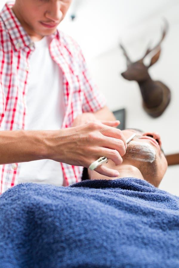 Mężczyzna dostaje goljący od fryzjera męskiego zdjęcie royalty free