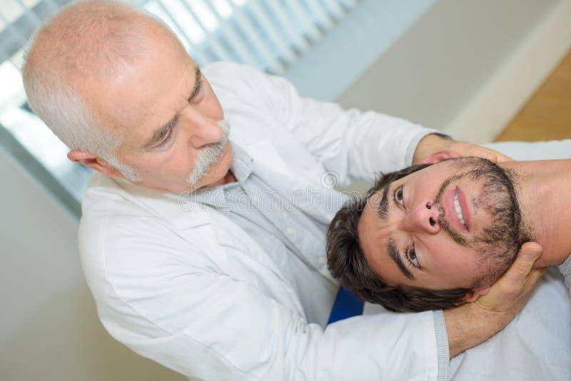 Mężczyzna dostawania głowy masaż w medycznym biurze obrazy royalty free