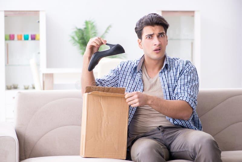 Mężczyzna dostawania krzywda pakuneczek z żeńskimi kobieta butami zdjęcia royalty free