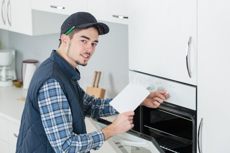 Mężczyzna dostosowywa nową kuchenkę w kuchni zdjęcia royalty free