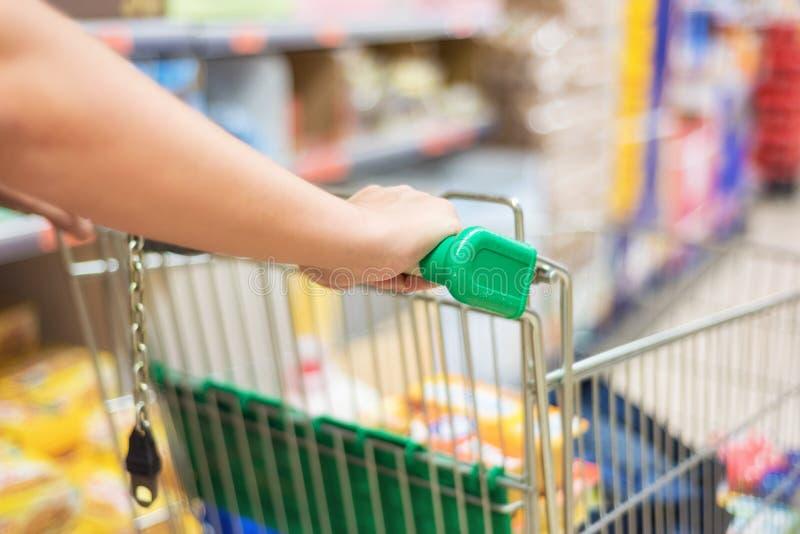Mężczyzna dosunięcia wózek na zakupy w supermarketa sklepu plamy abstrakcjonistycznym tle obraz stock