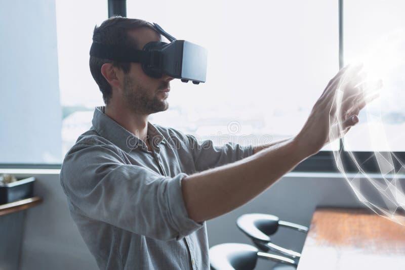 Mężczyzna dotyka 3D sfery interfejs w VR słuchawki obraz royalty free