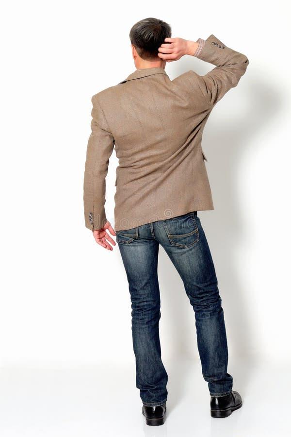 Mężczyzna drapa jego głowę na lekkim tle z powrotem zdjęcie stock