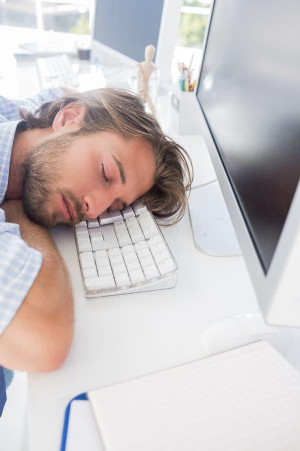 Mężczyzna drzemanie na jego biurku zdjęcie royalty free