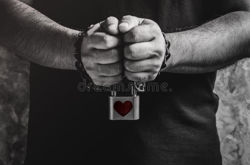 Mężczyzna dwa ręki przykuwającej z starym ośniedziałym łańcuchem i czerwieni sercem sh zdjęcie royalty free