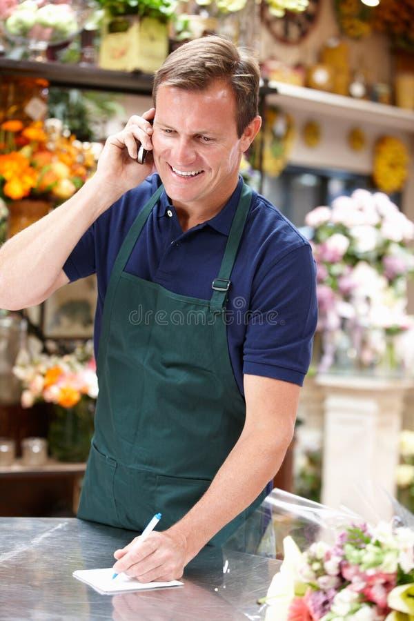 Mężczyzna działanie w kwiaciarni pozyci przy kontuarem zdjęcie royalty free