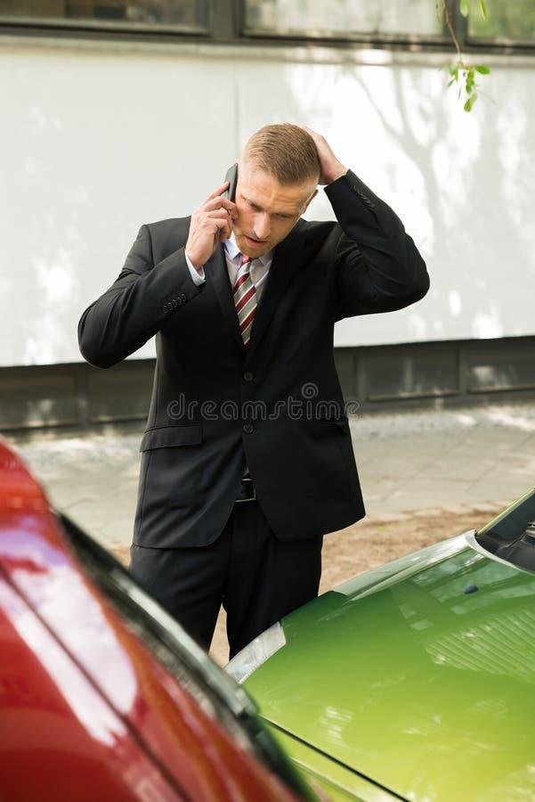 Mężczyzna dzwoni na telefonie komórkowym po wypadku samochodowego zdjęcia stock