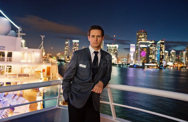 Mężczyzna ekonom na statek desce przy nocą w Miami, usa Macho w kostium kurtce na miasto linii horyzontu Wodny transport, transpo obraz stock