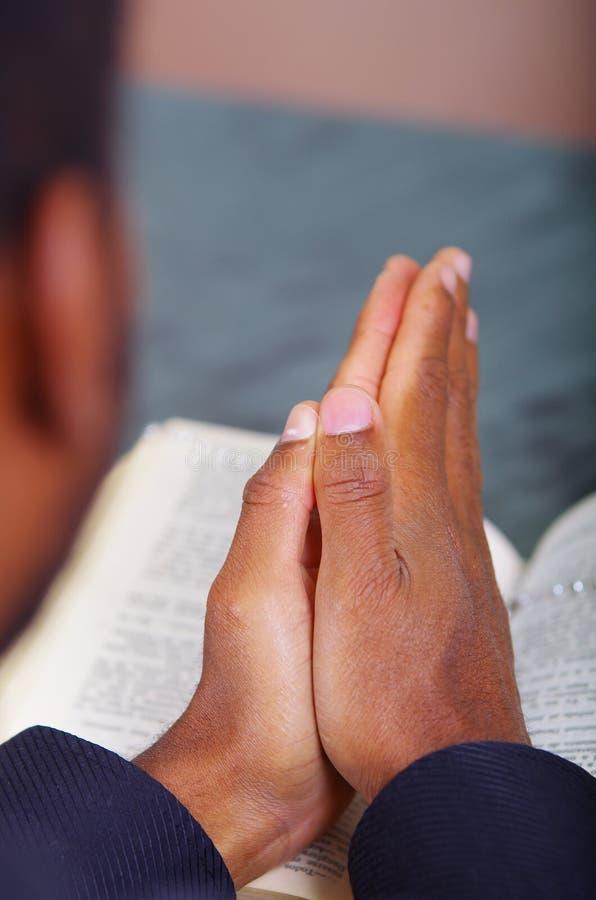 Mężczyzna falcowanie wręcza modlenie z otwartym biblii lying on the beach w przodzie, widzieć od behind model głowy, religii poję obraz stock