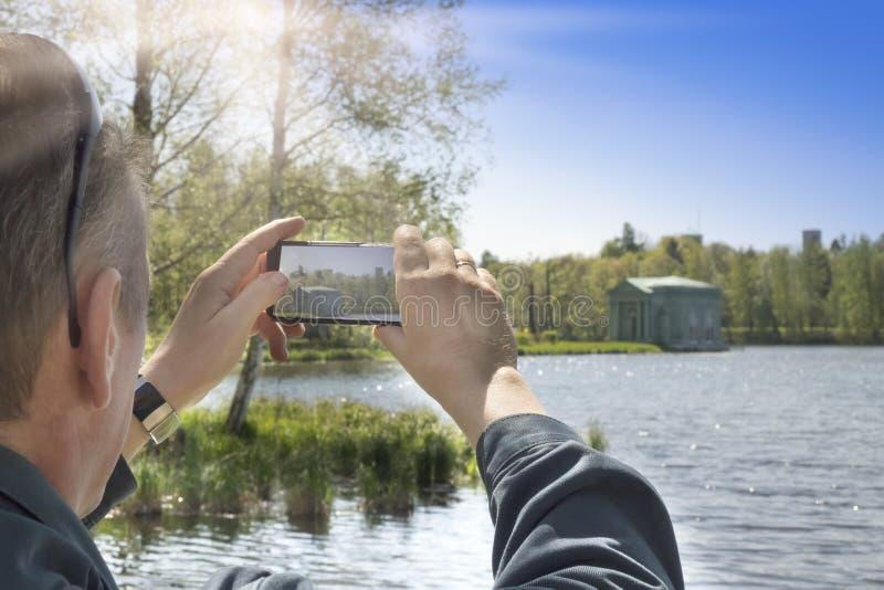 Mężczyzna fotografie na telefonie komórkowym na banku jezioro pawilon zdjęcia royalty free